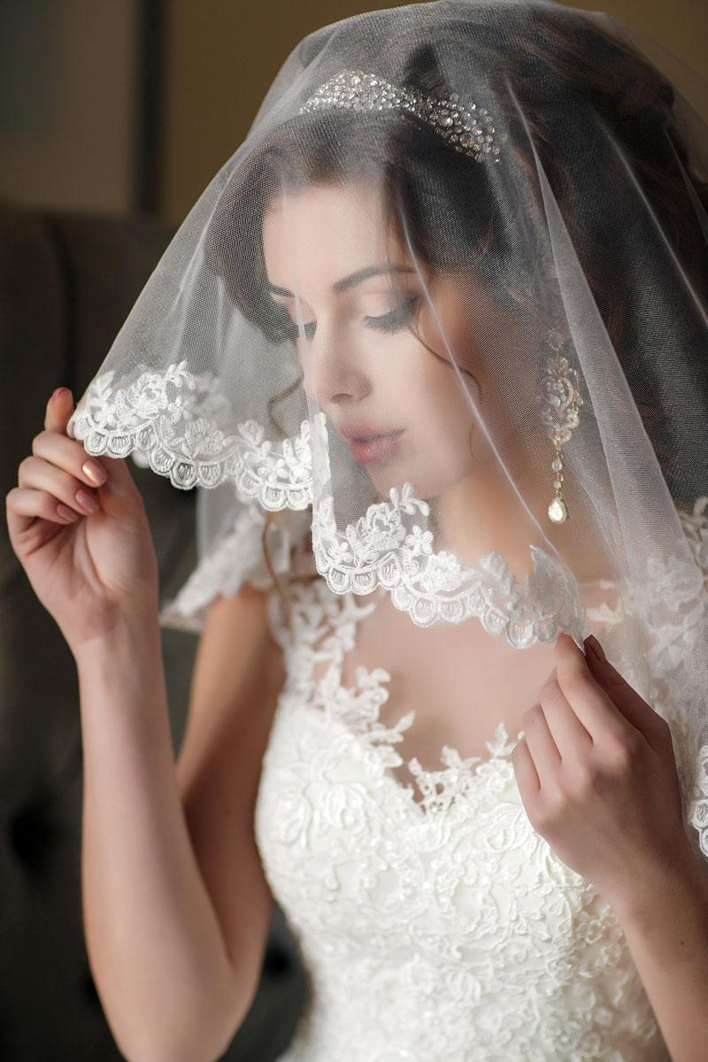 Невеста в фате смотрится в зеркало